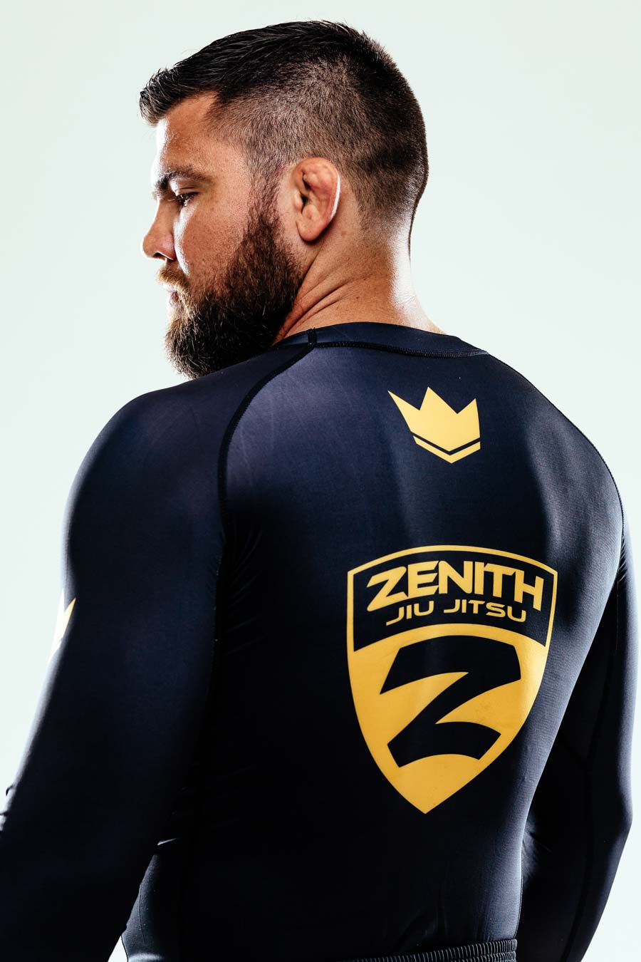 robert drysdale stands with his back to the camera looking over his left shoulder - the zenith jiu jitsu logo is on his back