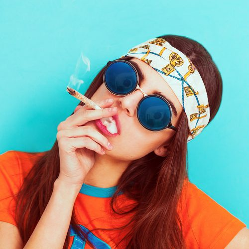 a young lady with sunglasses smokes a cannabis cigarette