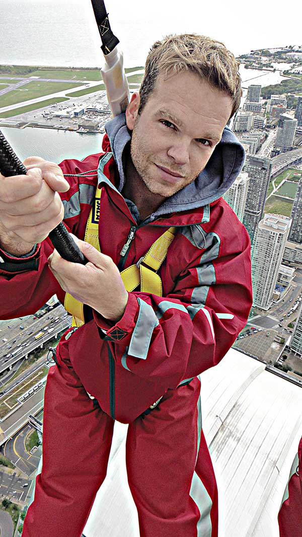 dave stands suspended from the edge of the CN tower in Toronto